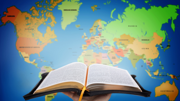 Bringing hope to the world. Open Bible in front of world map.