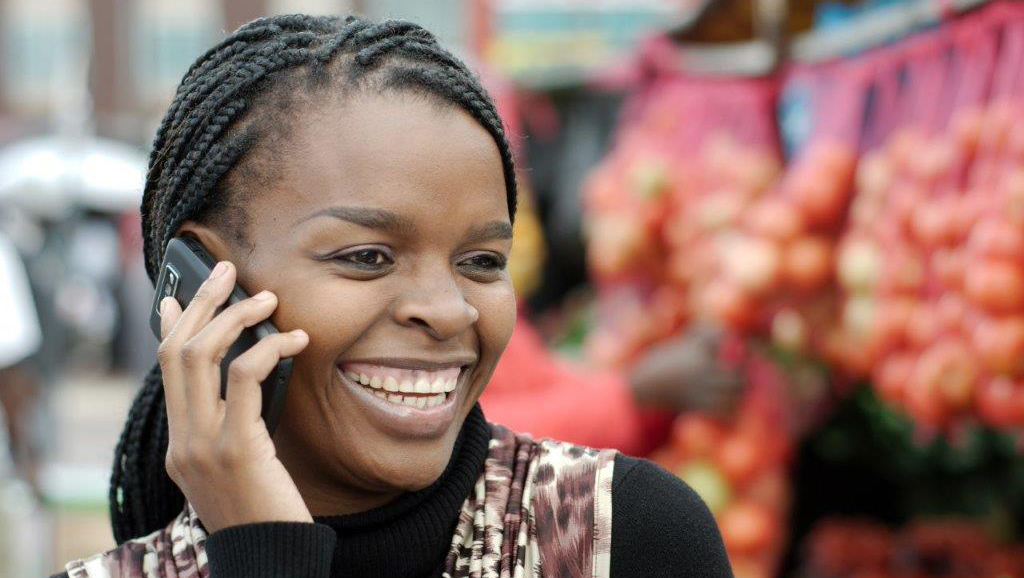 Woman listening to Women of Hope programming on cell phone