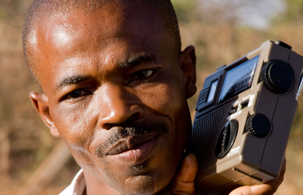 African man listening to a radio