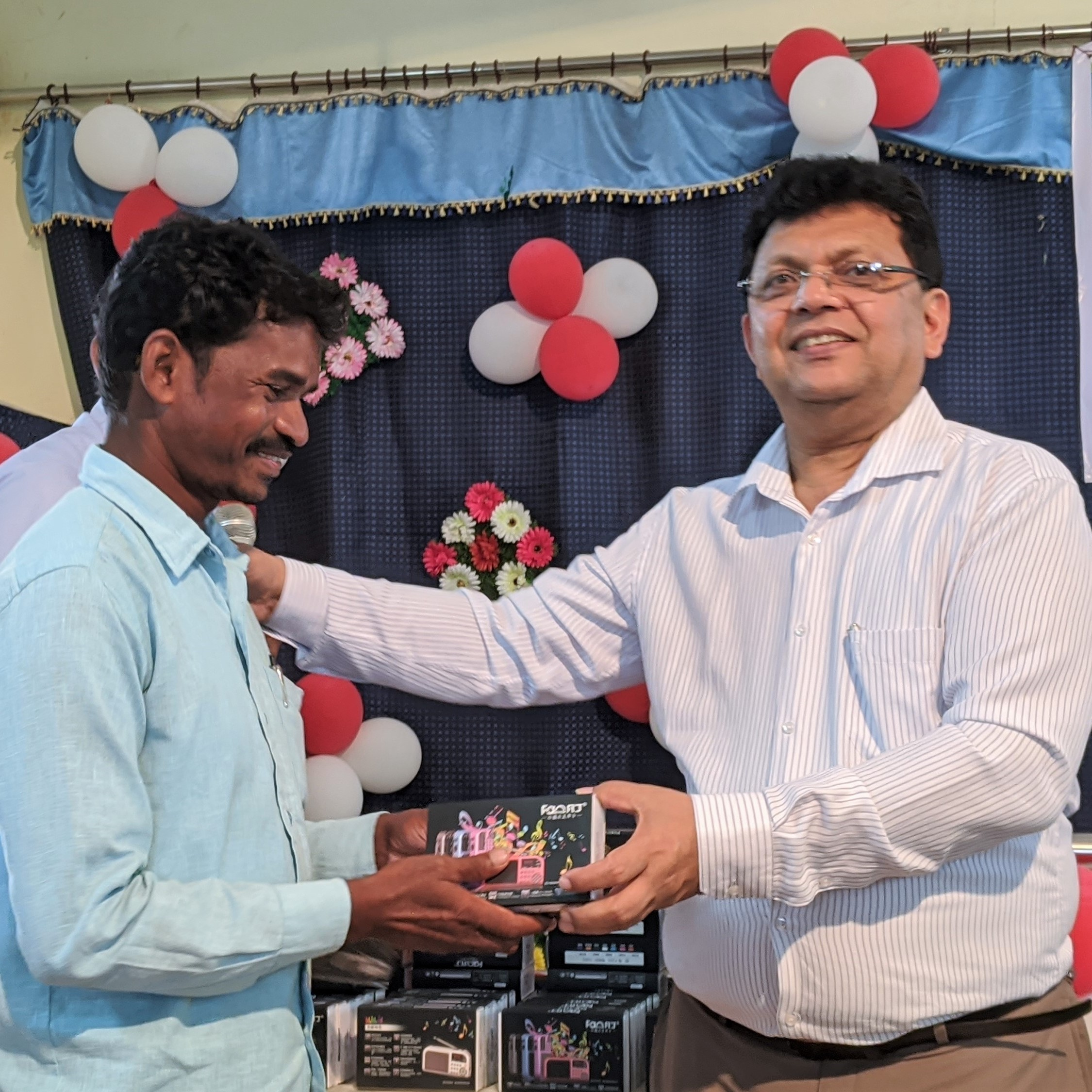 TWR India's George Philip gives a media player to a radio home group leader