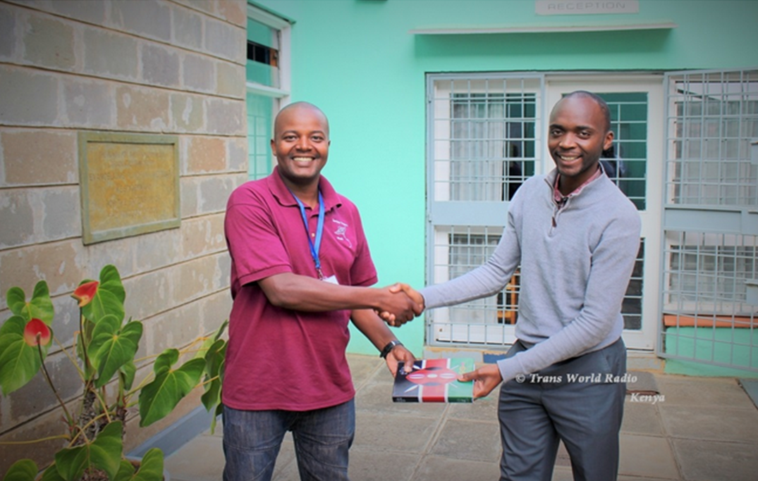 Joel receives his Bible from TWR Kenya staff.